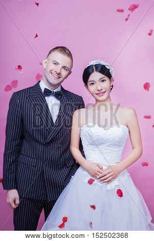 Portrait of happy wedding couple standing against pink background