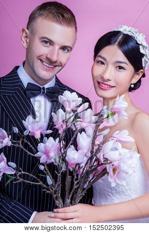 Portrait of smiling wedding couple holding artificial flowers against pink background