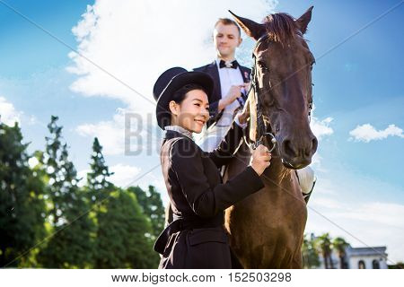 Side view of happy woman standing by man sitting on horse against sky