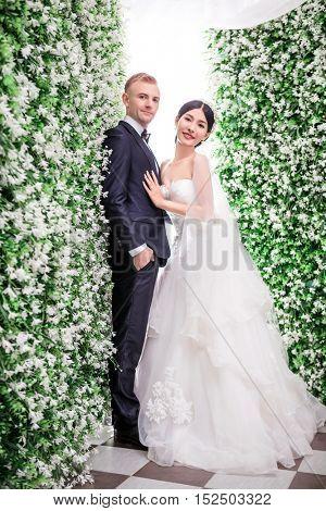 Portrait of romantic wedding couple standing amidst flower decorations