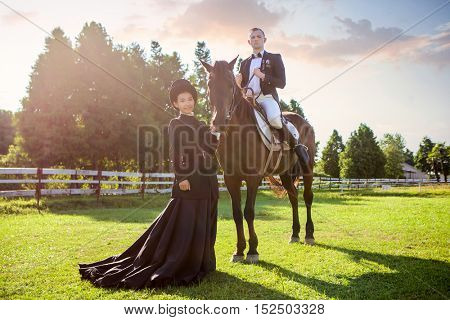 Portrait of woman standing by man sitting on horse at field during sunset