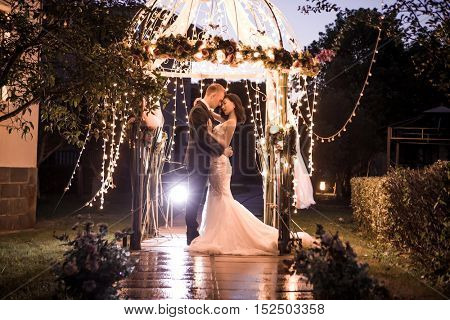 Elegant couple embracing in illuminated gazebo at night
