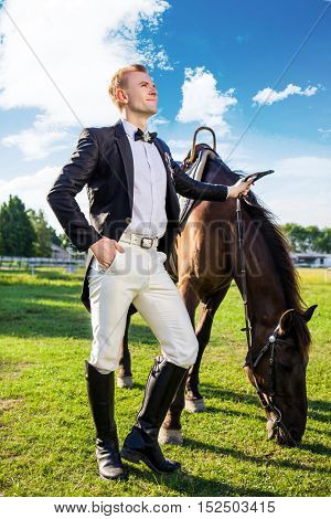 Full length of well-dressed man standing by horse on field