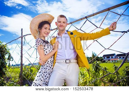 Portrait of happy couple standing by fence at field against sky