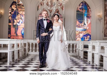 Portrait of confident wedding couple standing arm in arm at church