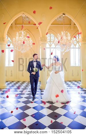 Full length of elegant wedding couple looking at each other while walking in church