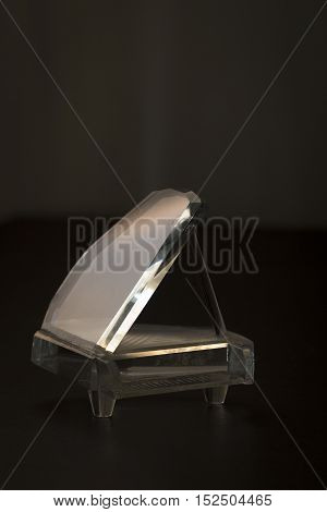 Glass figurine of a concert piano in the space scene.