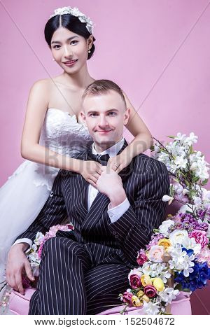 Portrait of confident wedding couple sitting against pink background