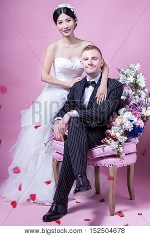 Portrait of elegant wedding couple sitting against pink background