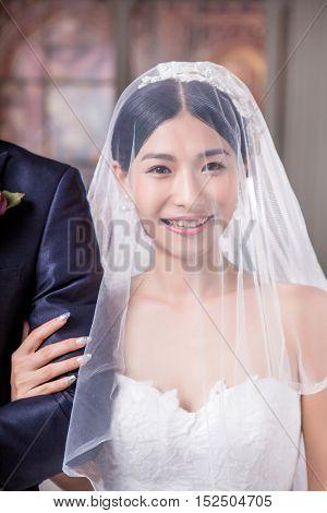 Portrait of happy bride standing with bridegroom in church