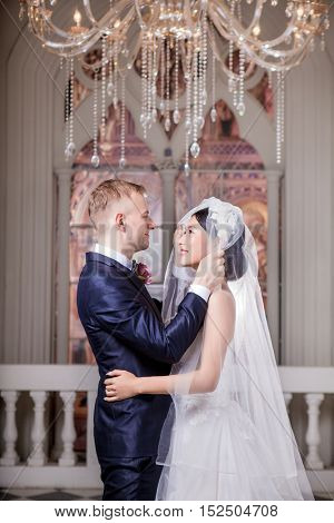 Side view of loving wedding couple looking at each other in church