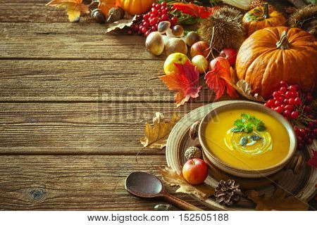 Thanksgiving autumn background with pumpkin soup on a wooden table