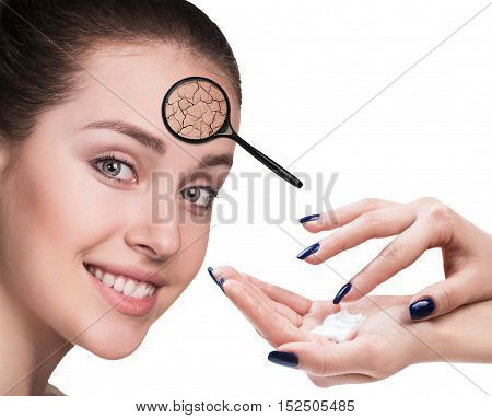 Hand applying cream on face of woman with dry skin. Concept of treatment and skin care.