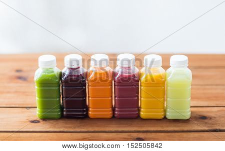 healthy eating, drinks, dieting and packaging concept - plastic bottles with different fruit or vegetable juices on wooden table