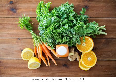 healthy eating, food, dieting and vegetarian concept - close up of bottle with carrot juice, fruits and vegetables on wooden table