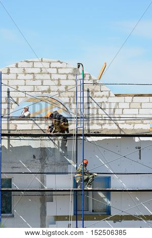 LYAKHOVICHI, BELARUS - AUGUST 28, 2016: Workers builders lift building materials on scaffolding