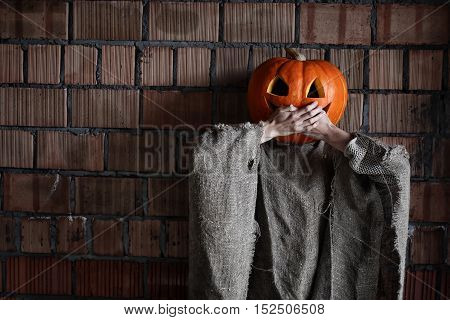 girl with a carved pumpkin on her head and on the body burlap outfit for Halloween