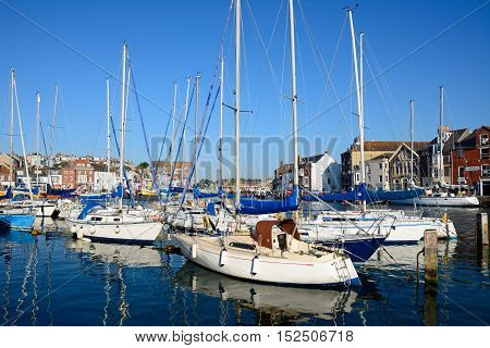 WEYMOUTH, UNITED KINGDOM - JULY 19, 2016 - Yachts moored in the harbour with quayside building to the rear Weymouth Dorset England UK Western Europe, July 19, 2016.