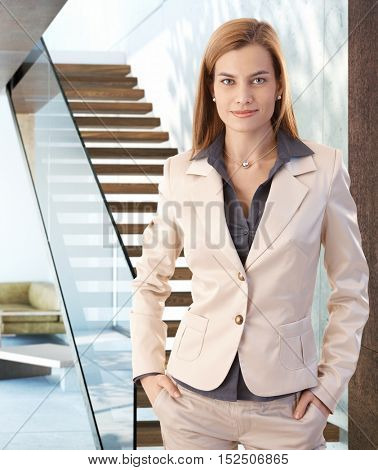 Confident young businesswoman standing with hands in pocket, looking at camera.