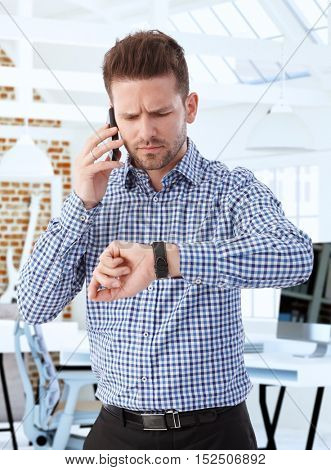 Businessman standing at office, looking at wristwatch anxious, using mobile.