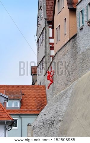 BESIGHEIM, GERMANY - APRIL 24, 2016: The wall of an old building with the modern sculpture of the red man crawling up. Besigheim, Baden-Wurttemberg, Germany.