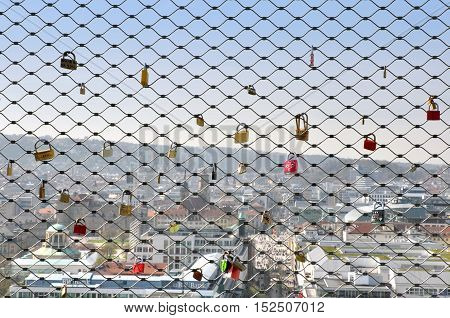 STUTTGART, GERMANY - APRIL 10, 2015: Metal mesh with padlocks on the background of the panorama of Stuttgart, Germany.