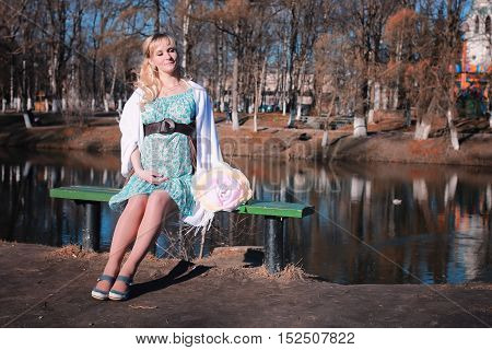 cute beautiful blonde pregnant woman walks in the park in the spring afternoon