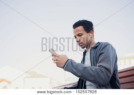African american young man in sports uniform and headphones is listening to music using a smartphone