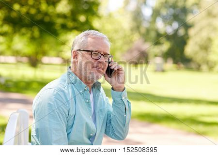 technology, senior people, and communication concept - happy old man dialing phone number and calling on smartphone at summer park