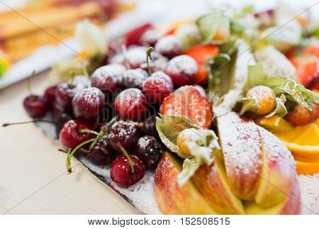 food, sweets and holidays concept - close up of dish with sugared fruit dessert