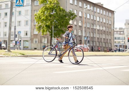 people, style, city life and lifestyle - young hipster man with shoulder bag and fixed gear bike crossing crosswalk on street