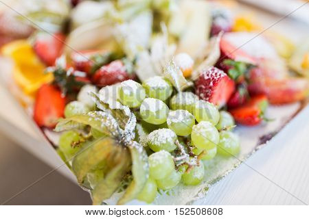 food, fruits, dessert and holidays concept - close up of dish with sugared grapes