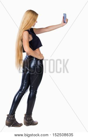 back view of standing young beautiful  girl with tablet computer in the hands of. girl  watching. Rear view people collection.  Isolated over white background. Blonde in leather pants makes selfie.