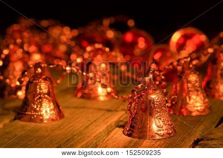 Garland from brilliant hand bells on a table. Hand bells of gold color Christmas decoration lighting from a candle stand on a table from old boards. Close up small depth of sharpness