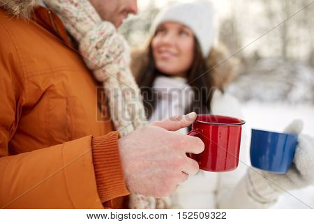 people, winter, drinks and season concept - close up of happy couple holding hot tea cups