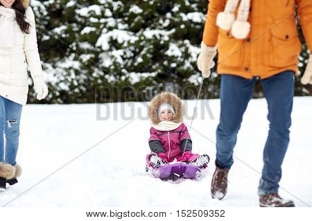 parenthood, fashion, season and people concept - happy family with child on sled walking in winter forest