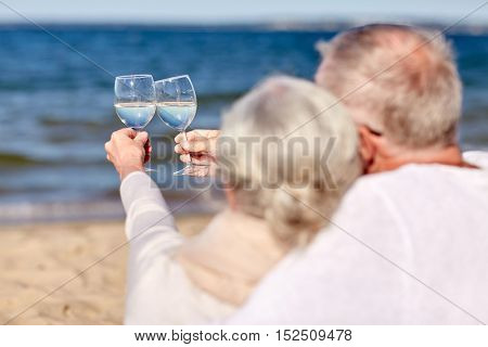 family, age, holidays, leisure and people concept - close up of happy senior couple clinking wine glasses on summer beach