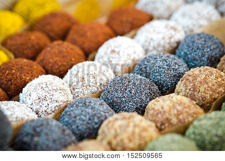 Colorful healthy homemade candies with nuts, dry fruits and spices, selective focus