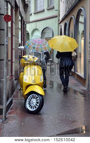 Colmar, France - April 23, 2016: The old narrow street in Colmar with yellow bike and pedestrian with a yellow umbrella.