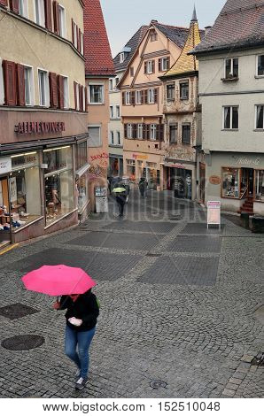 Tubingen, Germany - April 17, 2016: The narrow pedestrian street with old half-timbered houses. A man with a pink umbrella in the foreground. Baden-Wurttemberg, Germany.