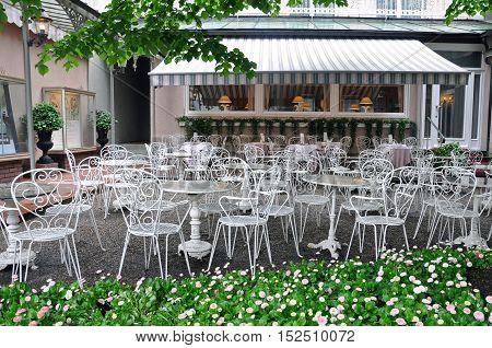 Baden-Baden, Germany - April 27, 2014: Empty street cafe of Baden-Baden with white decorative elegant tables and chairs.