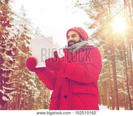 christmas, season, technology and people concept - happy man with tablet pc computer in winter forest