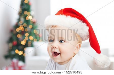 childhood, holidays and people concept - beautiful little baby boy in christmas santa hat over living room with christmas thee lights background