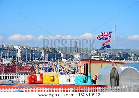 WEYMOUTH, UNITED KINGDOM - JULY 18, 2016 - View along the beach and promenade with a Super Snails childrens ride in the foreground Weymouth Dorset England UK Western Europe, July 18, 2016.
