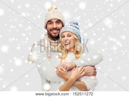 winter, fashion, couple, christmas and people concept - smiling man and woman in hats and scarf hugging over snow background