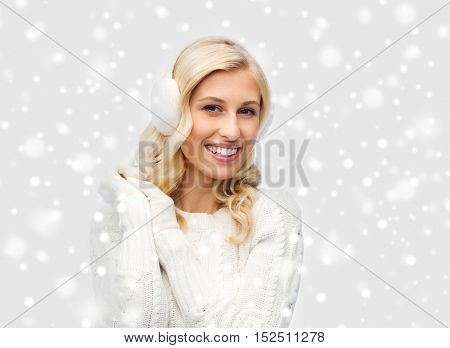 winter, fashion, christmas and people concept - smiling young woman in earmuffs and sweater