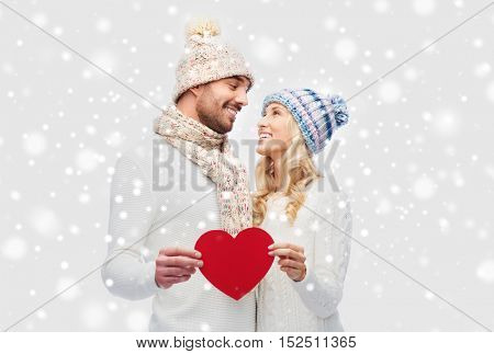 love, valentines day, couple, christmas and people concept - smiling man and woman in winter hats and scarf holding red paper heart shape