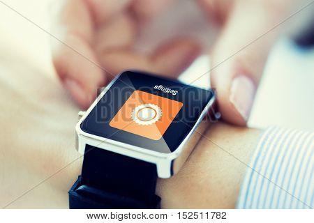 business, technology, settings and people concept - close up of woman hands with cogwheel icon on smartwatch screen