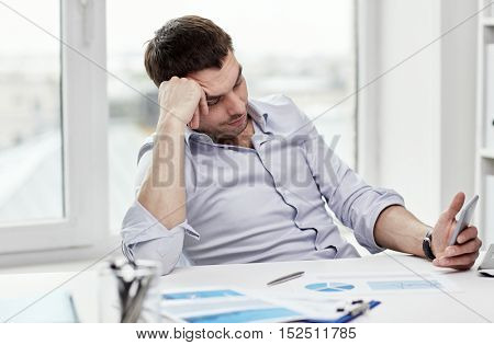 business, people and technology concept - businessman with smartphone and papers at office