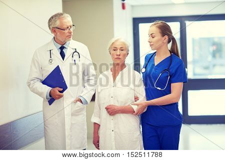medicine, age, health care and people concept - male doctor with clipboard, young nurse and senior woman patient going down corridor at hospital